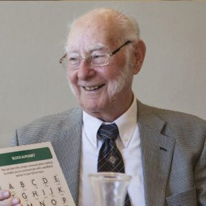 Elderly Man holding a fingerspelling chart